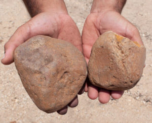 Large river rock in hands close up