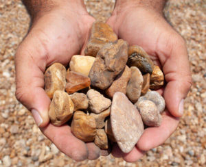 small river rock in hands close up